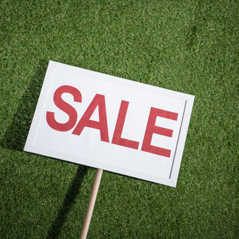 white sale banner lying on green grass, house for sale concept
